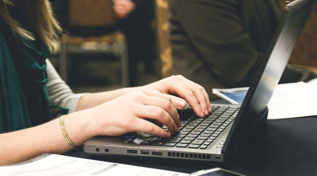 Photo of a person's hands typing on a laptop keyboard