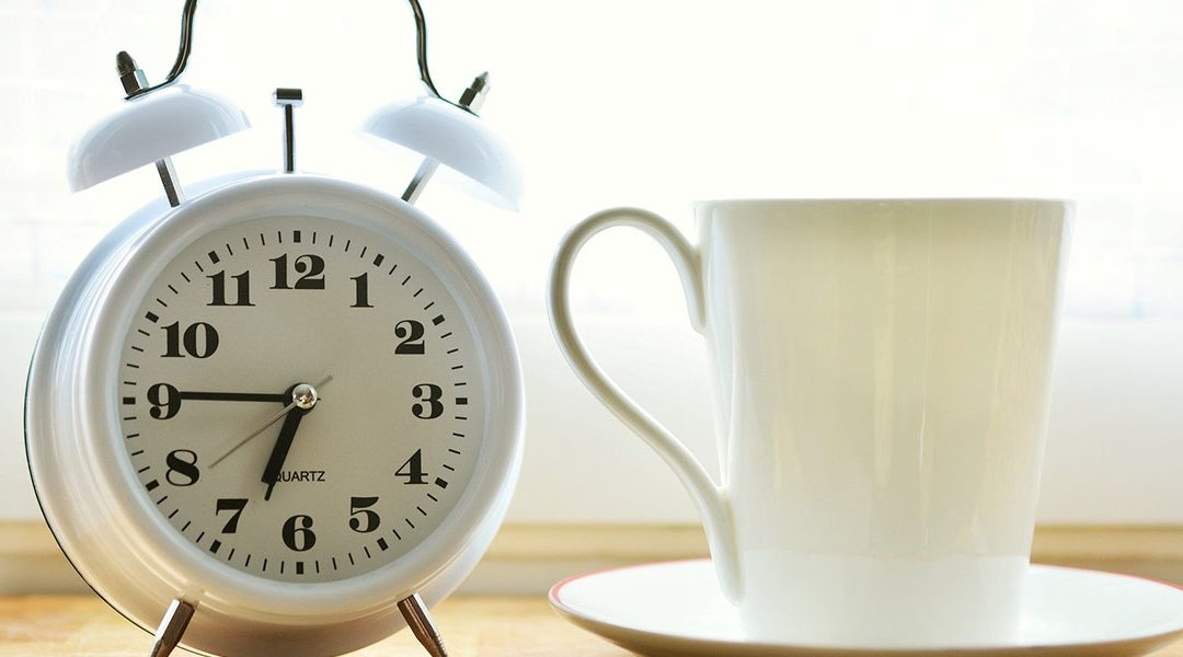 Alarm clock with tea cup beside it