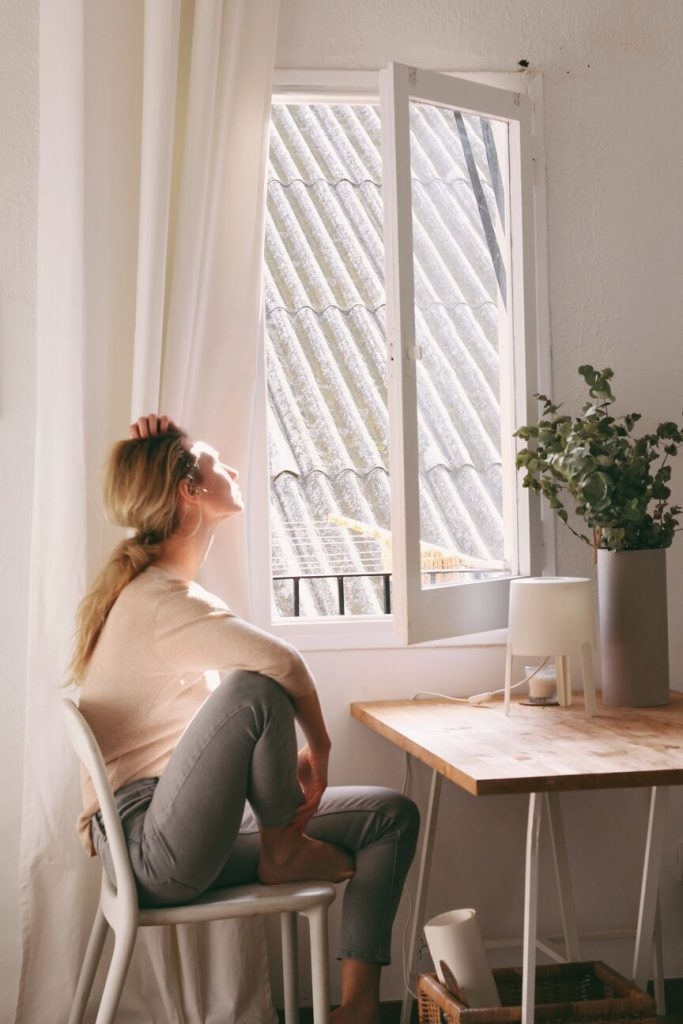 woman looking out of a window who has lost her mojo